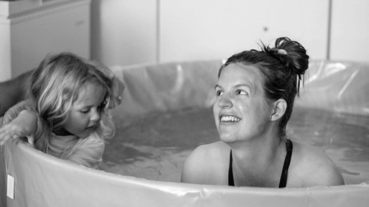 Laboring in the tub with daughter before water birth.